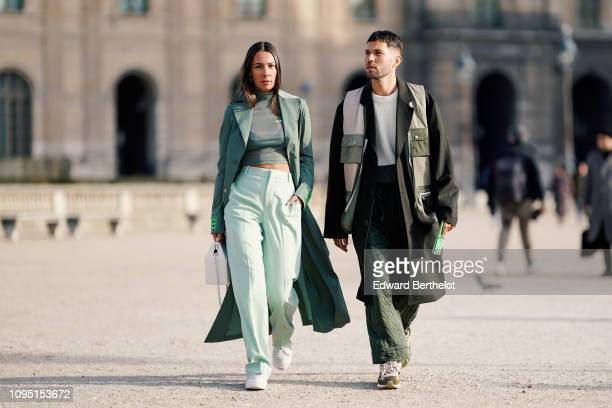 Alice Barbier wears a green trench coat a green cropped top flare pants JeanSebastien Rocques wears a khaki long coat green flare pants sneakers...