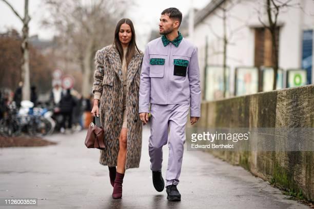 Alice Barbier wears a leopard print coat a brown leather bag JeanSebastien Rocques wears a purple jacket pants outside Jacquemus during Paris Fashion...