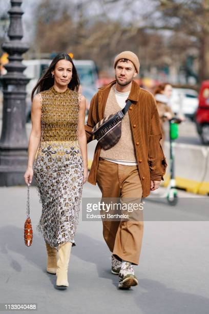 Alice Barbier wears a metal mesh fishnet over a floral print dress, a brown leather and metal mesh bag, beige pointy high-heeled boots ;...