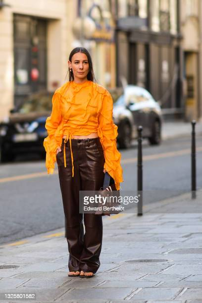 Alice Barbier wears an earring, an orange cropped top with long sleeves and large embroidery and pleats, brown leather pants, a brown leather bag,...