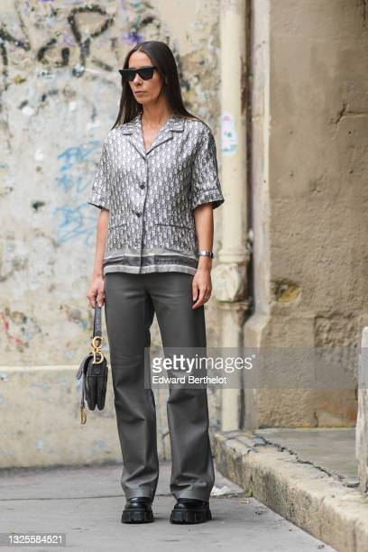 Alice Barbier wears black sunglasses, gold and diamond earrings, a white and pale gray Dior oblique jacquard monogram silk short sleeves shirt, a...