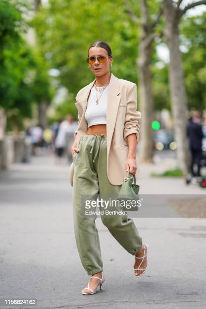 Alice Barbier wears earrings, sunglasses, necklaces, a white crop top, a beige jacket, pistachio green pants with a sliding belt and elastic leg...