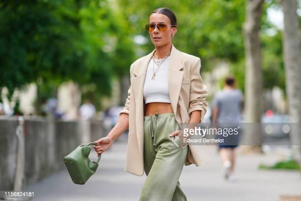 Alice Barbier wears earrings sunglasses necklaces a white crop top a beige jacket pistachio green pants with a sliding belt a pistachio green handbag...