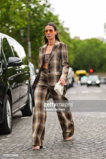 Alice Barbier wears orange sunglasses, silver and gold earrings, a gold CD buckle necklace from Christian Dior, a beige and brown oblique Dior...