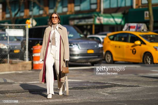 Alice Barbier wears sunglasses a trench coat a checked turtleneck top a white shirt white flowing pants shoes a Fendi monogram bag outside Sies...