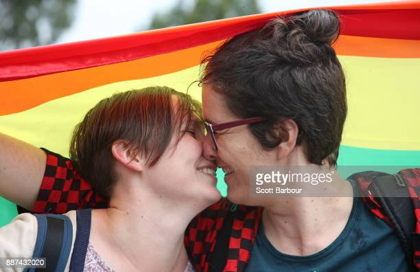 Alice Bennett and her partner Miranda Hill kiss as they gather with a crowd of people to watch a large television screen at Federation Square as it...