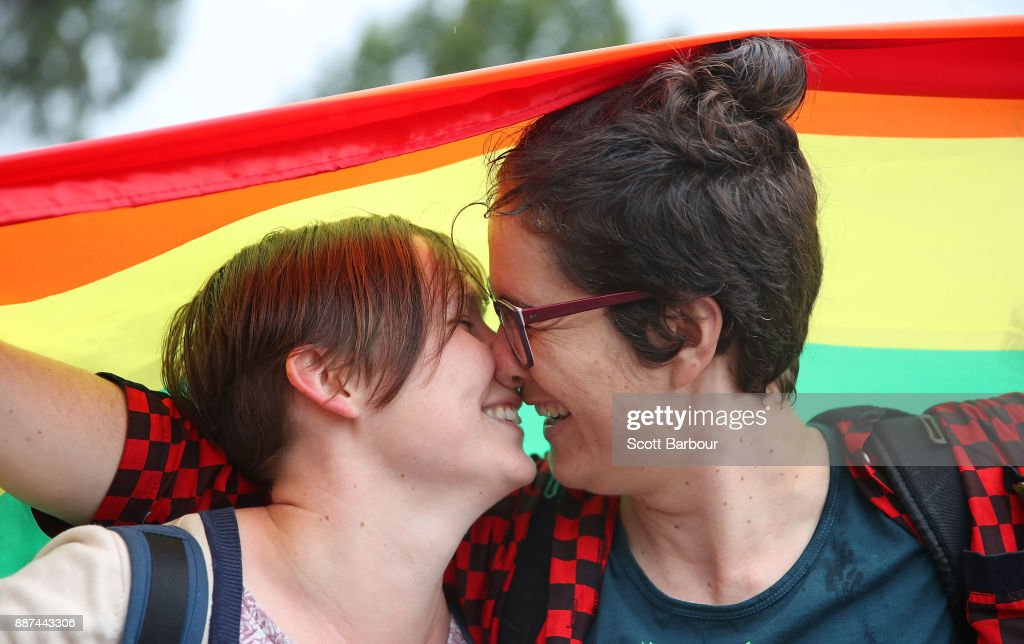 Alice Bennett and her partner Miranda Hill kiss as they gather with a crowd of people to watch a large television screen at Federation Square as it is announced that same-sex marriage will be legal in Australia with Parliament agreeing to change the Marriage Act and end the ban on gay and lesbian couples marrying on December 7, 2017 in Melbourne, Australia. The historic bill was passed on the final day of parliamentart sitting for 2017. The legislation means same-sex couples will now be able to be legally married in Australia. Australians voted 'Yes' in the Marriage Law Postal Survey for the law to be changed in November.