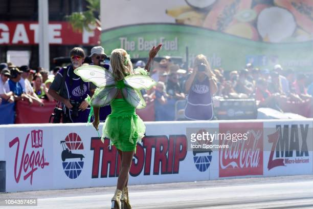 Alice Bode in costume directs husband Bob Bode Ford Mustang NHRA Funny Car into staging for the third round of qualifying for the 18th Annual Toyota...