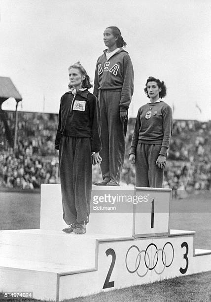 Alice Coachman of the US along with the winner DJ Tyler of Great Britain and MOM Ostermeyer of France stand on a podium at Wembley Stadium to receive...