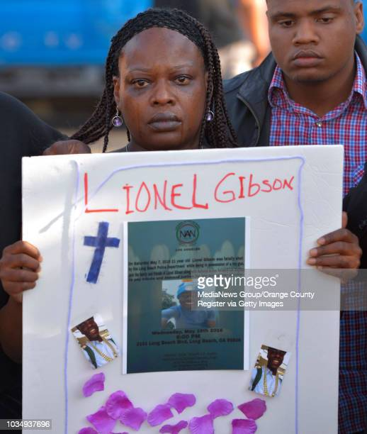 Alice Corley the mother of Lionel Gibson holds a sign as she attends a vigil for Gibson in Long Beach CA on Wednesday May 18 2016 A couple dozen...