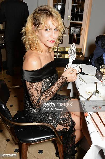 Alice Dellal poses with art by Clym Evernden at the Charlotte Olympia 'Handbags for the Leading Lady' launch dinner at Toto's Restaurant on October...