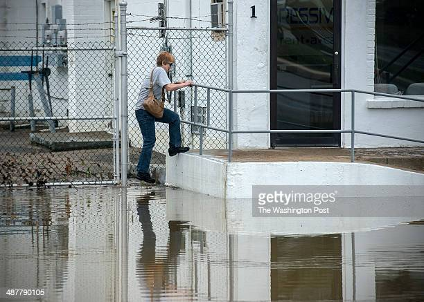 Alice Ellis makes her way back to her apartment after being evacuated before dawn due to flooding on Main street on May 2014 in Laurel MD