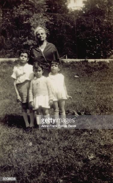 Alice FrankStern mother of Otto Frank grandmother of Anne Frank standing on a lawn with her grandchildren Stefan Margot and Bernd Frank Frankfurt am...