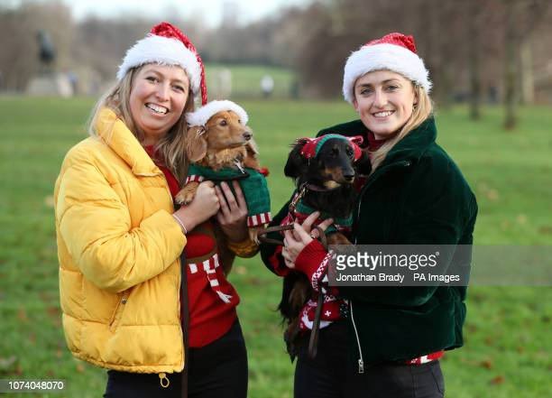 Alice Hancock with her dachshund Nutmeg and Lucy Hughes with her dachshund Twiglet attend a sausage dog festive walk in Hyde Park, London.