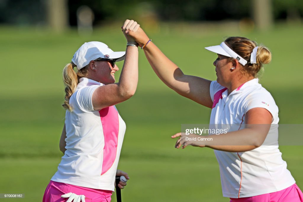 Alice Hewson (R) of the Great Britain and Ireland Team celebrates with India Clyburn on the 10th green after Clyburn had holed a putt to save the hole in their match against Jennifer Kupcho and Lilia Vu of the United States team during the afternoon foursomes matches in the 2018 Curtis Cup Match at Quaker Ridge Golf Club on June 8, 2018 in Scarsdale, New York.