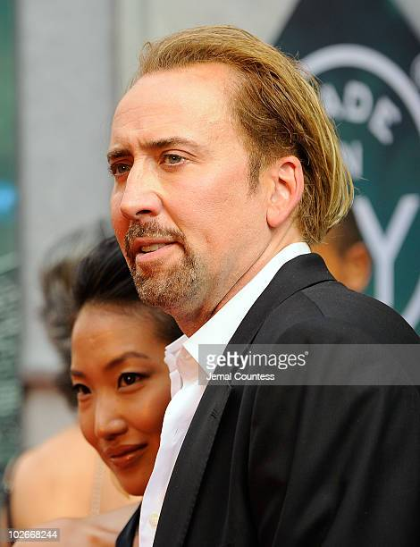 Alice Kim and actor Nicolas Cage pose for a photo on the red carpet at the premiere of The Sorcerer's Apprentice at the New Amsterdam Theatre on July...