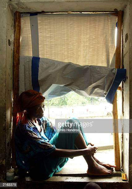 Alice Morsay a Sierra Leonian refugee sits in a doorway of a Masonic temple converted into a refugee camp July 15 2003 in Monrovia Liberia Liberia is...