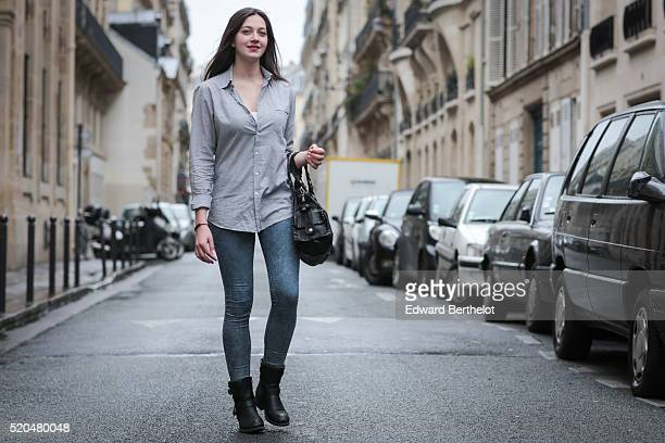 Alice Mouzon is wearing a Silverado Chloe black bag a The Kooples gray shirt Zara blue jeans and black boots during a street style session on April...