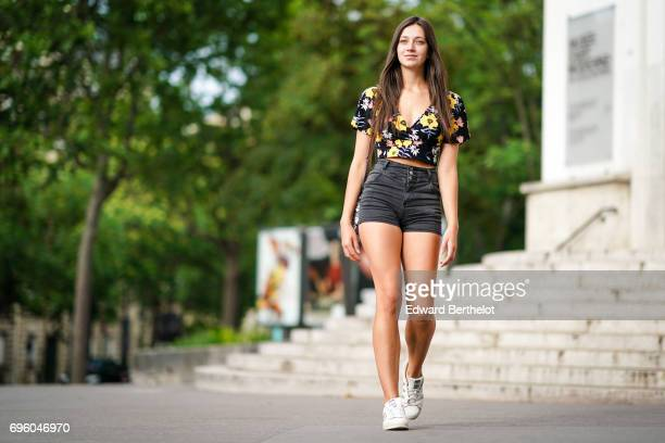 Alice Mouzon wears a Hetm low neck bare belly flower print tshirt a Primark black denim short Adidas Stan Smith sneakers shoes and a silver bag on...