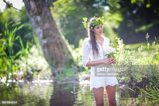 Alice Mouzon wears a Lovie Co white lace playsuit a crown made of flowers in a lake at Chateau de Saint Antoine on June 2 2017 in Limoges France