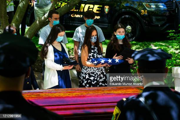 Alice Roberts holds a flag alongside her children during the funeral of her husband Glen Ridge Police Officer Charles Roberts after he passed away...