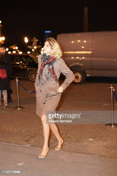 Alice Taglioni wears a colorful floral print fringed scarf, a light brown trench coat, shiny golden heeled sandals, on April 12, 2019 in Paris,...