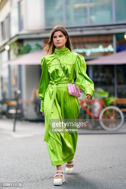 Alice Violier wears a green silky lustrous turtleneck dress with puff long sleeves, a pink mesh bag, white shoes, outside Paco Rabanne, during Paris...