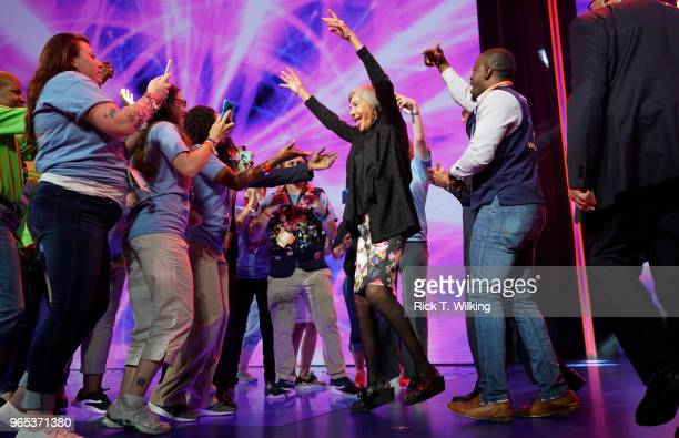 Alice Walton daughter of Walmart founder Sam Walton dances with Walmart associates onstage during the annual shareholders meeting event on June 1...