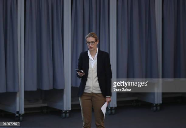 Alice Weidel of the right-wing Alternative for Germany political party holds a mobile phone as she attends debates at the Bundestag over a proposal...