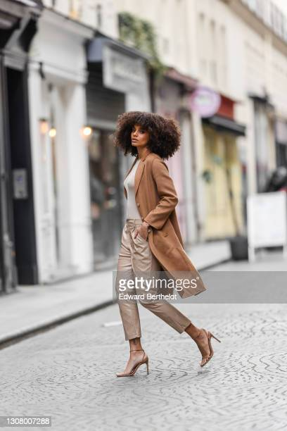 Alicia Aylies, Miss France 2017, wears a brown / beige wool long coat, a gray top, beige leather pants, high heels shoes / sandals, on March 19, 2021...