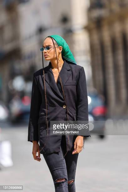 Alicia Aylies wears a green bandanna scarf with printed polka dots over the head, blue sunglasses, a black oversized blazer jacket, black skinny...