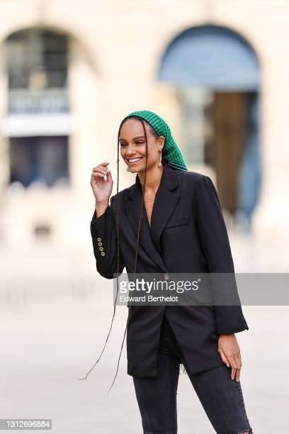 Alicia Aylies wears a green bandanna scarf with printed polka dots over the head, a black oversized blazer jacket, black skinny ripped denim jeans...