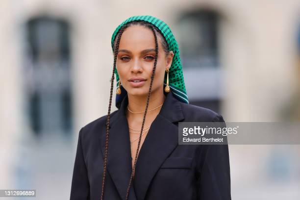 Alicia Aylies wears a green bandanna scarf with printed polka dots over the head, a black oversized blazer jacket, on April 15, 2021 in Paris, France.