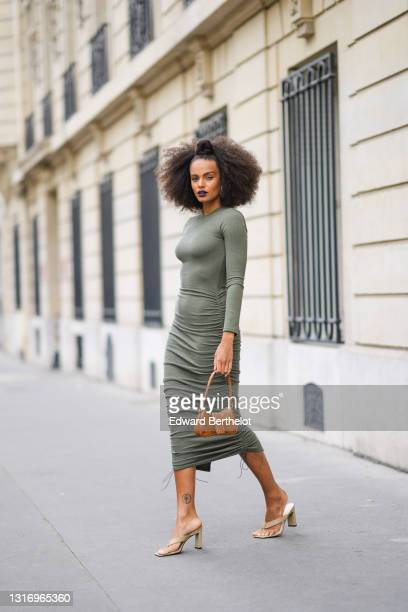 Alicia Aylies wears a green midi dress, a brown leather bag with crocodile pattern, beige sandals shoes, on April 29, 2021 in Paris, France.