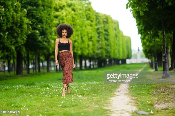 Alicia Aylies wears a necklace, a black cropped tank top, a brown leopard print flowing midi skirt, high heels shoes, on April 21, 2021 in Paris,...