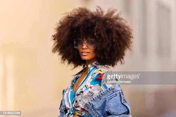 Alicia Aylies wears silver Gucci sunglasses, a silver chains necklace, a white and blue pattern silk knotted Roberto Cavalli shirt, a blue faded...