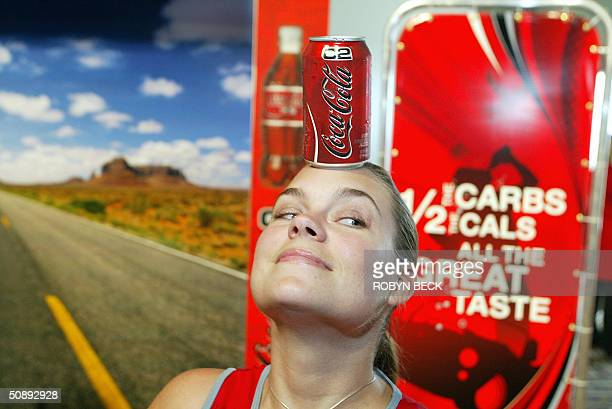 Alicia Corbett balances a can of the new CocaCola C2 lowcarb soft drink on her head at the product's US launch in the Hollywood section of Los...