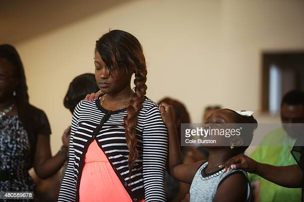 Alicia Jesquith mother of the late Lecent Ross victim of a shooting earlier this week closes her eyes during a prayer to end evils at their Rexdale...