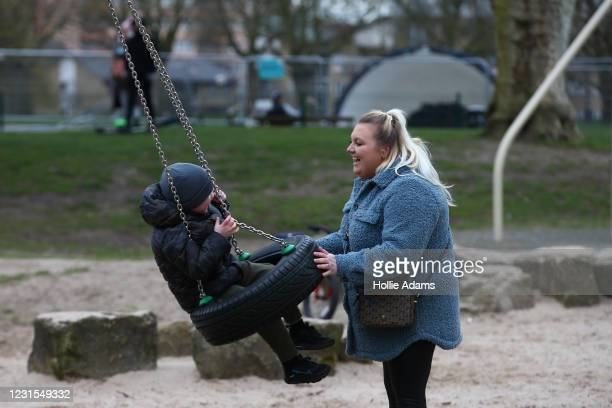 Alicia Large pushes her son Bobby Norfolk on a swing at Victoria Park playground on March 6, 2021 in London, England. Londoners are enjoying bright...