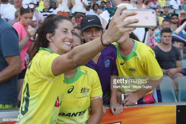 Alicia Quirk of Australia poses for a selfie with a person in the crowd after winning the womens bronze cup match between New Zealand and Australia...
