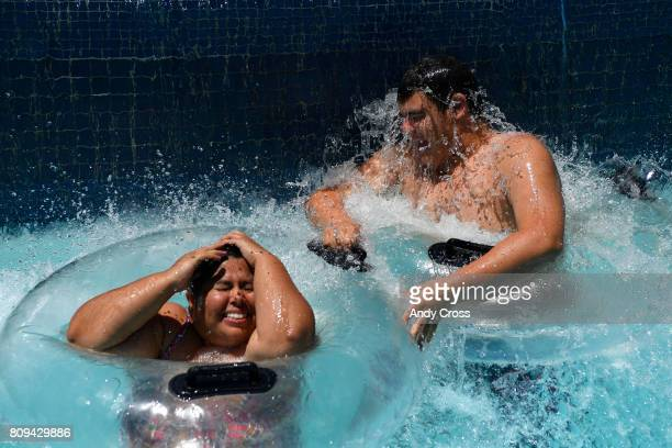 Alicia Rodriguez left and her nephew Caleb Mauldin cool off in the The River under a waterfall at Pirates Cover Waterpark in near record temperatures...
