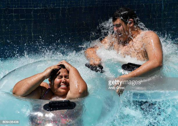 Alicia Rodriguez left and her nephew Caleb Mauldin cool off in the The River under a waterfall at Pirates Cove Waterpark in near record temperatures...