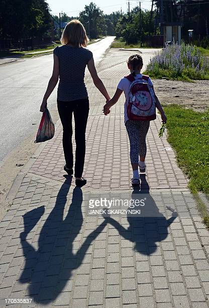 Alicja Pietrucha and her mother Ilona are seen on their way to primary school on June 14 2013 Kuligow Poland AFP PHOTO/JANEK SKARZYNSKI