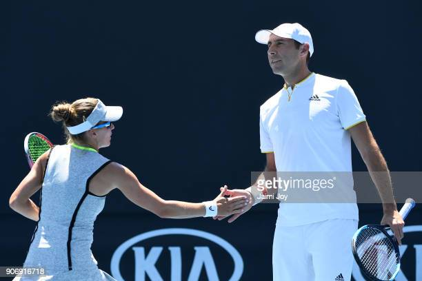 Alicja Rosolska of Poland and Santiago Gonzalez of Mexico talk tactics in their first round mixed doubles match against Johanna Larsson of Sweden and...