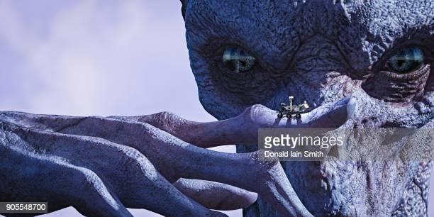 Alien examining tiny vehicle on finger