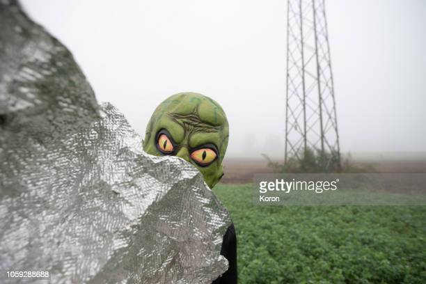 alien hiding behind an alien objest - alien stock photos and pictures