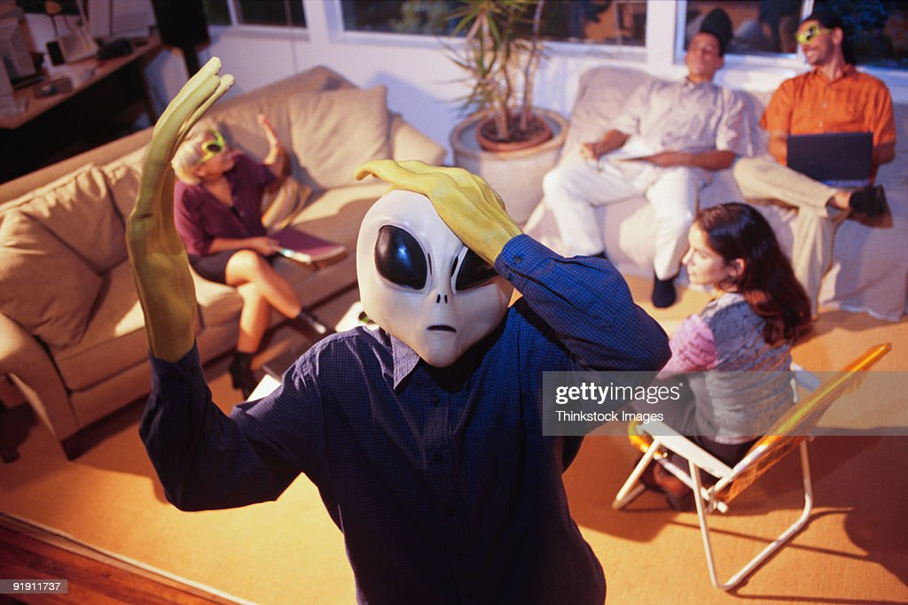Alien in foreground, hands to head, people seated on couch and chairs in background : Stock Photo