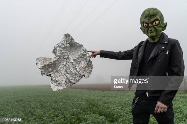 alien touching an alien object - alien stock photos and pictures
