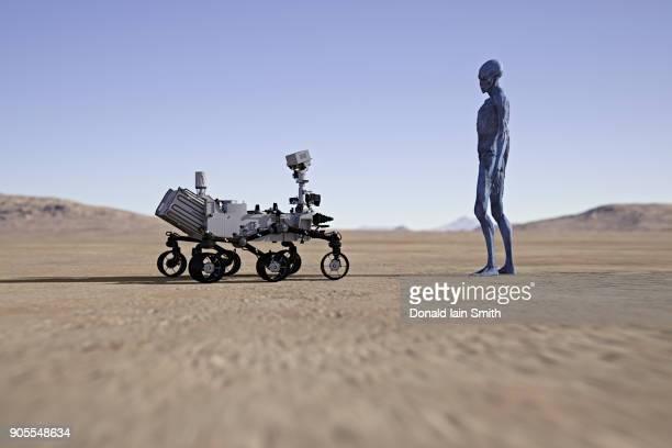 alien watching small vehicle in desert - außerirdischer stock-fotos und bilder