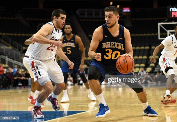Alihan Demir of the Drexel Dragons dribbles against Matty McConnell of the Robert Morris Colonials in the first half during the game at PPG Paints...